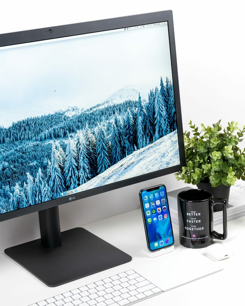Un monitor de pantalla plana de LG sentado en un escritorio al lado de un teclado, un smartphone y una taza