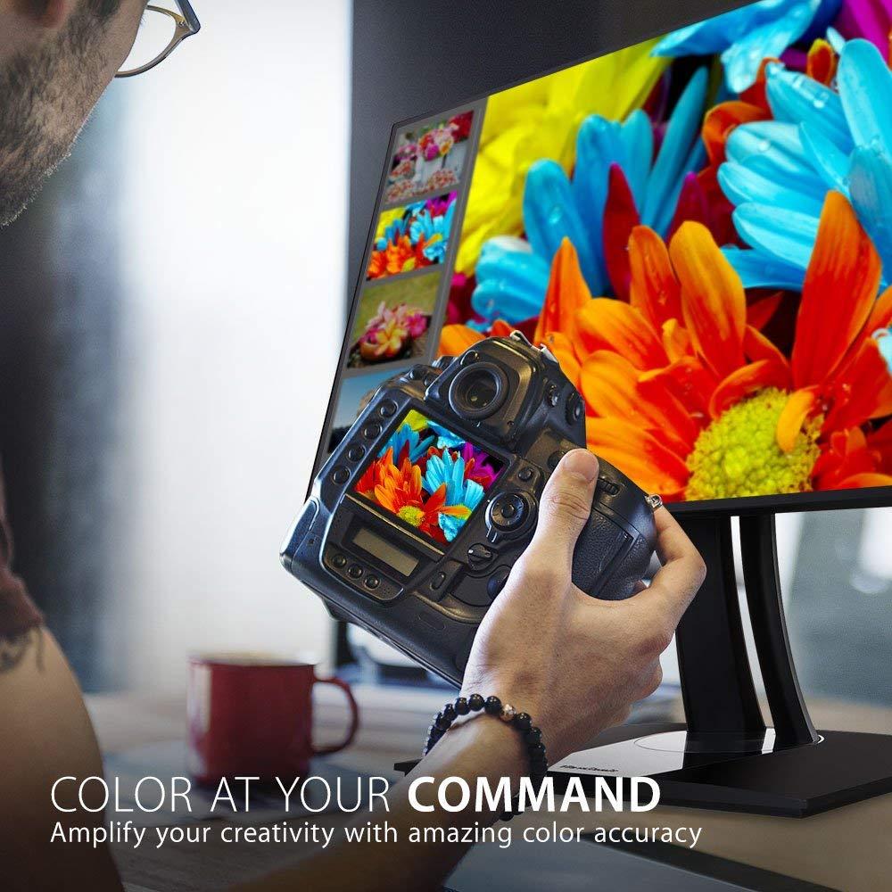Un hombre compara los colores de la parte trasera de su cámara DSLR con los del monitor de su ordenador
