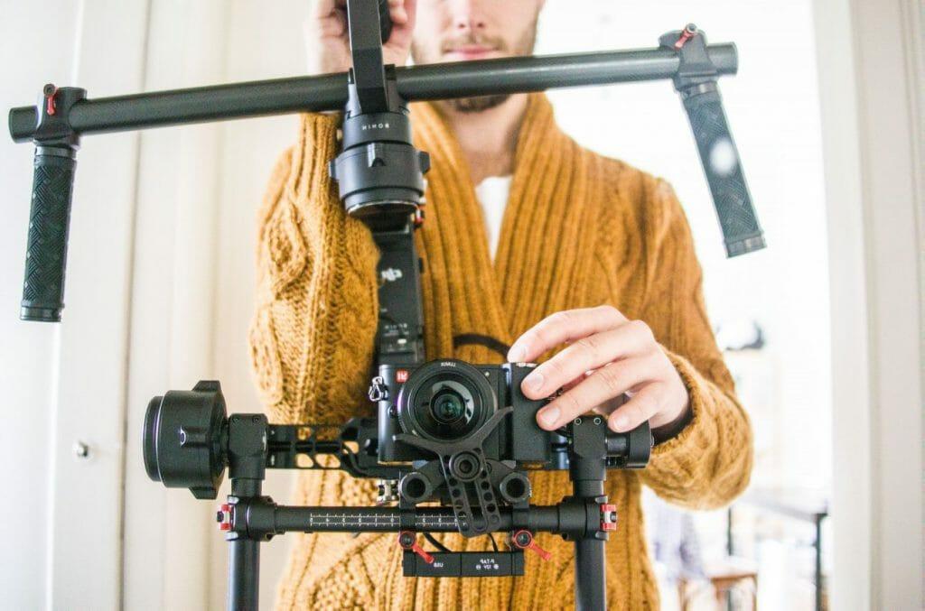 Un hombre con un suéter naranja ajusta un cardán con una cámara conectada a él.
