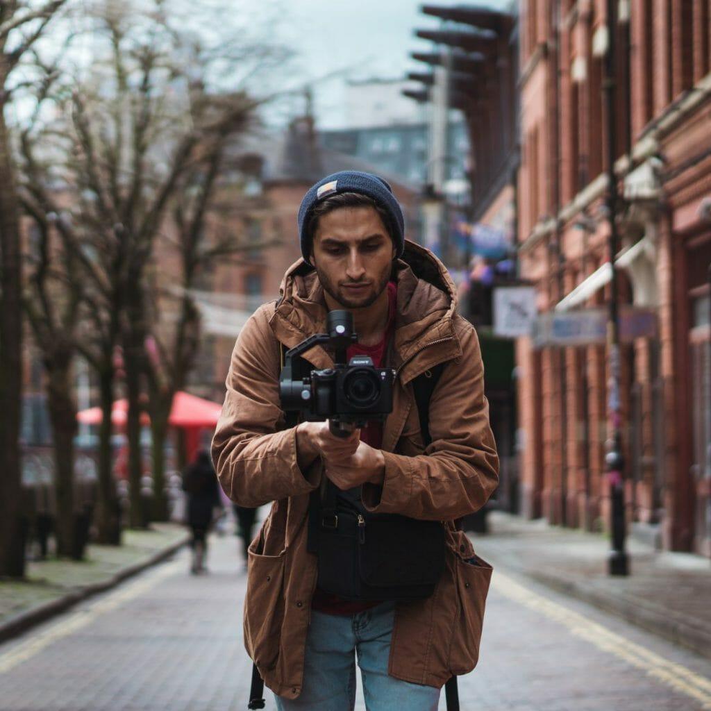 Un hombre en la calle usando un cardán con una cámara adjunta