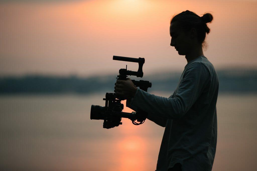Un hombre con la silueta de un atardecer, filmando con una cámara en un cardán.
