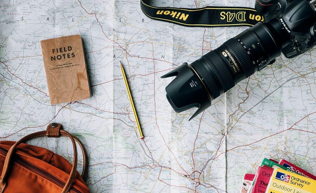 Una cámara Nikon con un teleobjetivo incorporado se sentó sobre un mapa de papel, junto con un lápiz, un cuaderno de notas de campo, otros mapas y una bolsa