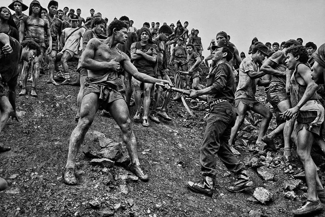 Una imagen en blanco y negro de dos hombres que parecen estar discutiendo, por el famoso fotógrafo Sebastião Salgado