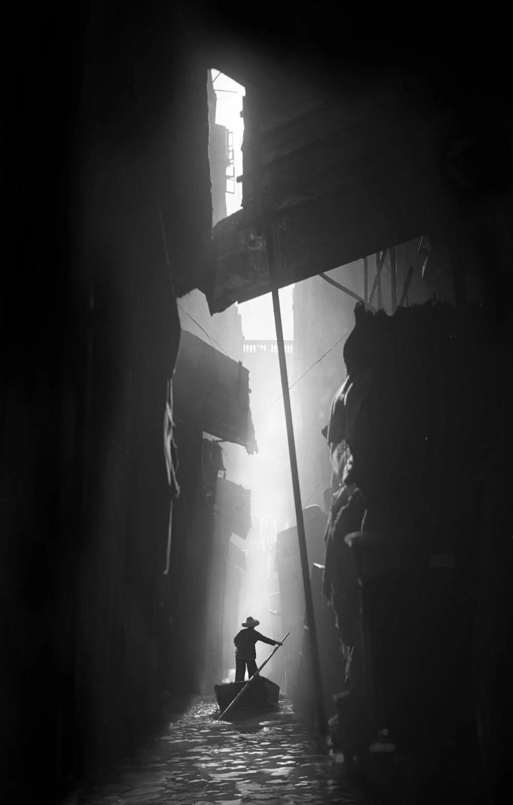 Una imagen en blanco y negro de un hombre en un barco en un río de Hong Kong por una estrecha vía fluvial, por el famoso fotógrafo Fan Ho