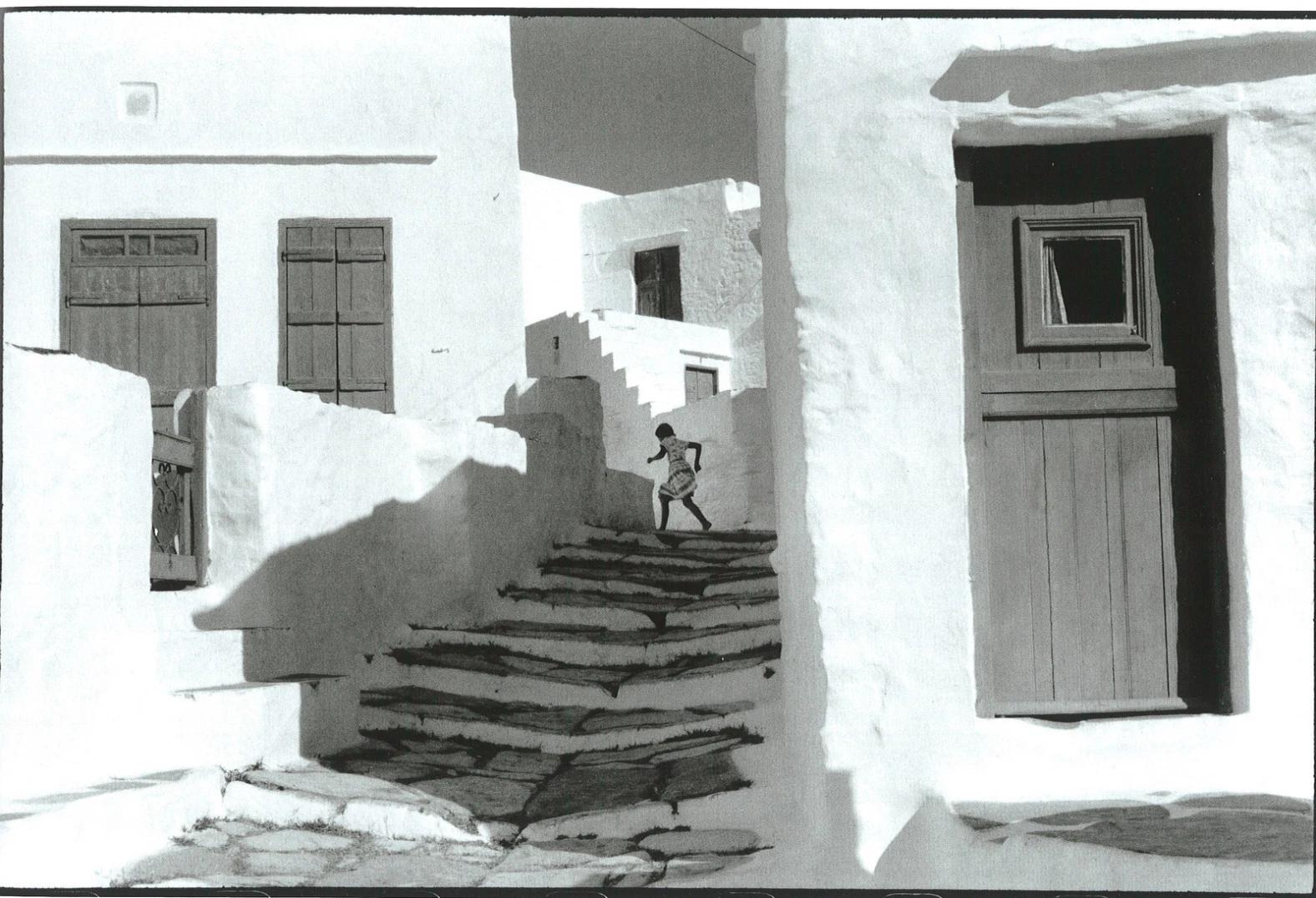 Una imagen en blanco y negro de un niño subiendo una escalera en un pueblo blanco, por el famoso fotógrafo Henri Cartier-Bresson
