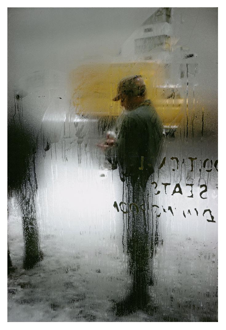 La imagen de un hombre parado frente a una ventana de vapor de Saúl Leiter