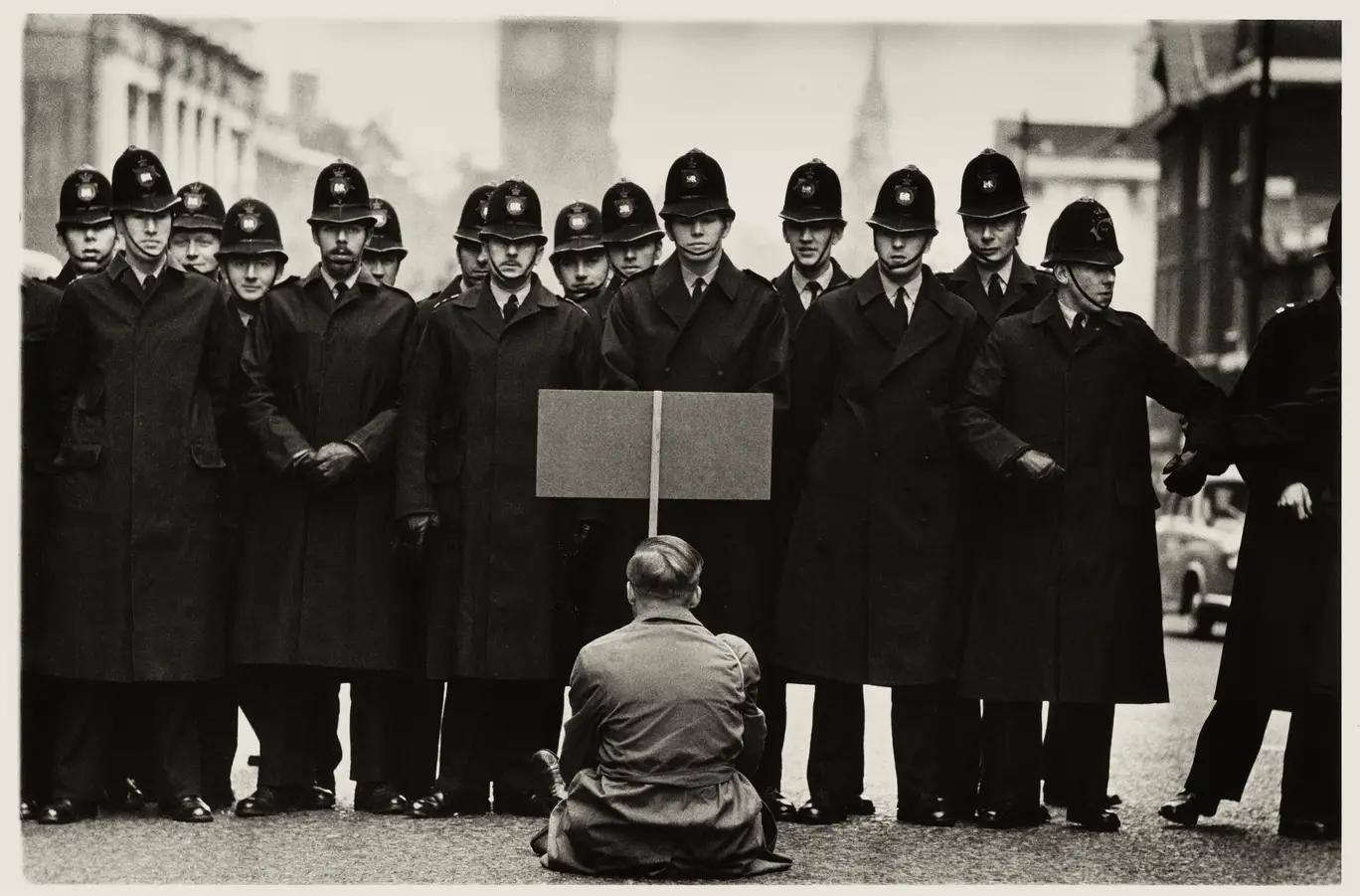 Una foto en blanco y negro de un solo manifestante sentado frente a una línea de la policía, del famoso fotógrafo Don McCullin