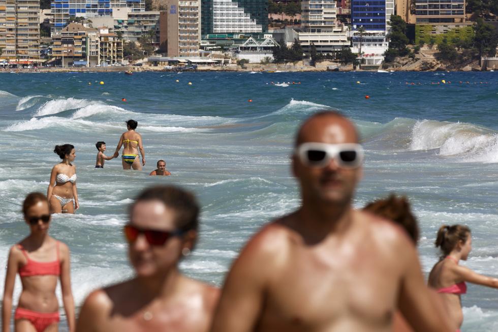 Una foto de veraneantes caminando por una playa y nadando en el mar por Martin Parr