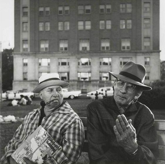 Una imagen en blanco y negro de dos hombres sentados en un banco teniendo una discusión por Vivian Maier