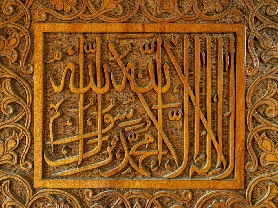 Inscripciones en árabe sobre una puerta de madera tallada a mano en Tashkent, Uzbekistán