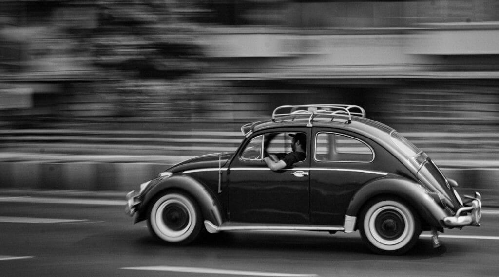 Una foto panorámica en blanco y negro de un coche VW Beetle en movimiento