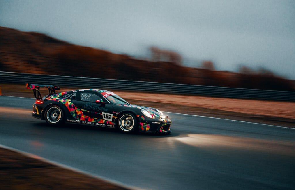 Una foto panorámica de un coche de carreras al atardecer acelerando en una pista de carreras