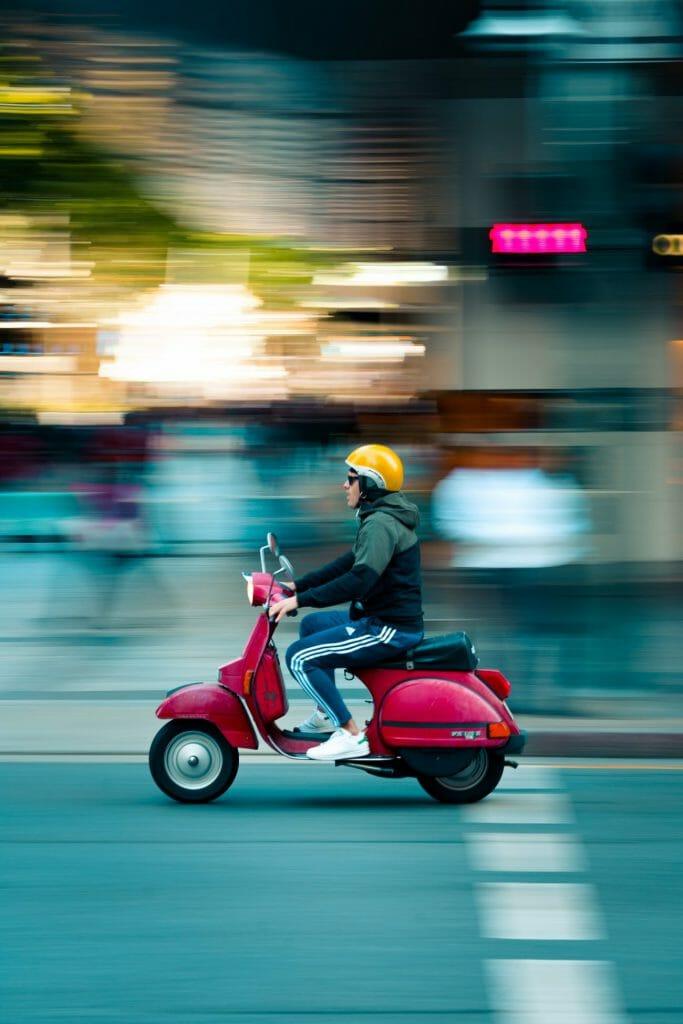 Una foto panorámica de un ciclomotor viajando por una carretera