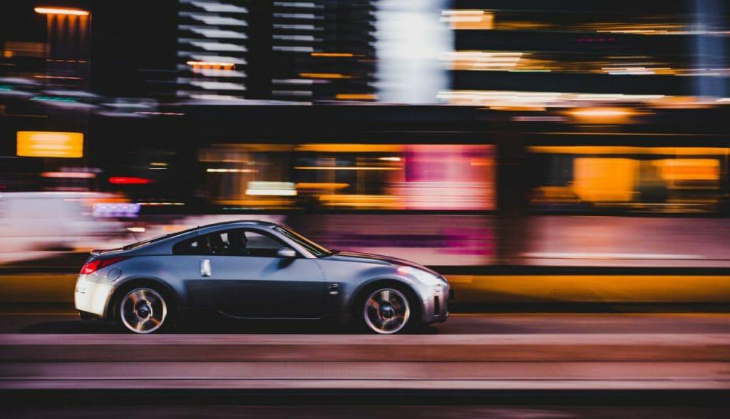 Una foto panorámica de un coche deportivo conduciendo por una carretera de noche