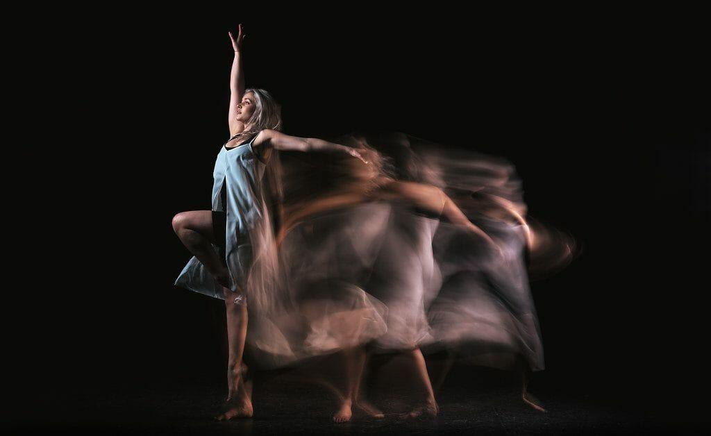 Una toma panorámica tomada con un flash de sincronización trasera de una bailarina