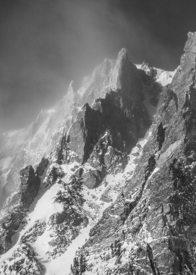 Esta es una dura fotografía en blanco y negro de un paisaje de invierno. Los bordes dentados de la montaña se adaptan bien a la intensidad de las condiciones climáticas de frío.