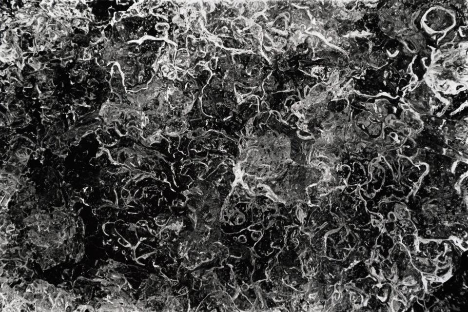 La nieve y el hielo son grandes sujetos de macrofotografía abstracta de cerca. Esta foto en blanco y negro muestra burbujas en un trozo de hielo.