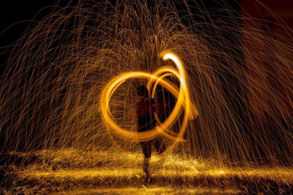 Un hombre gira la lana de acero encendida para crear efectos de luz