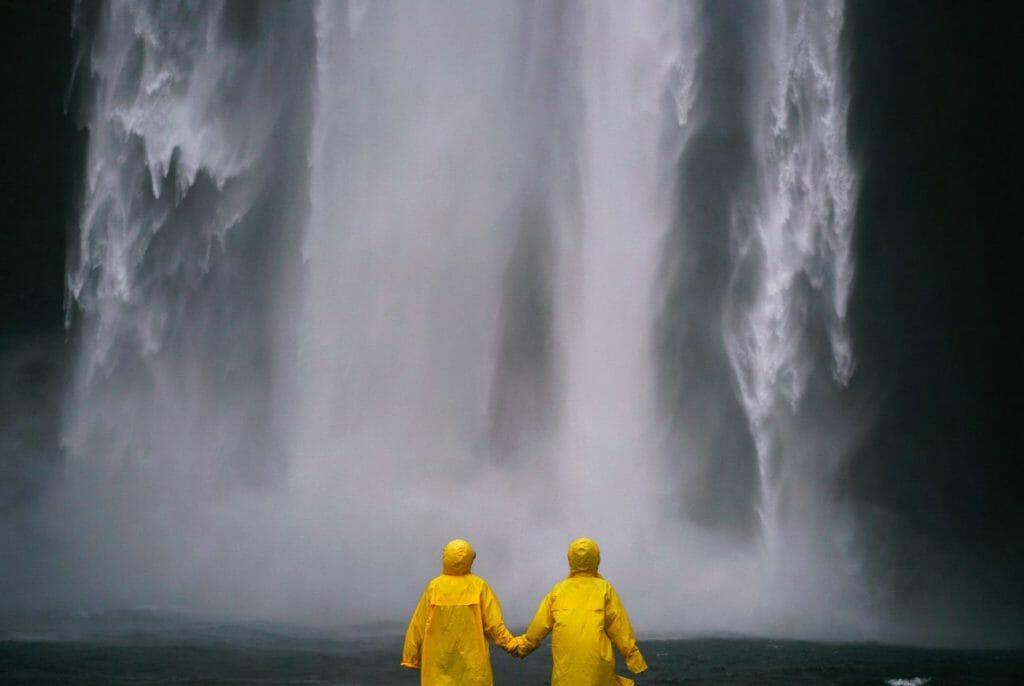 Una selección de colores de 2 personas con impermeables amarillos frente a una cascada en blanco y negro - una gran idea de fotografía