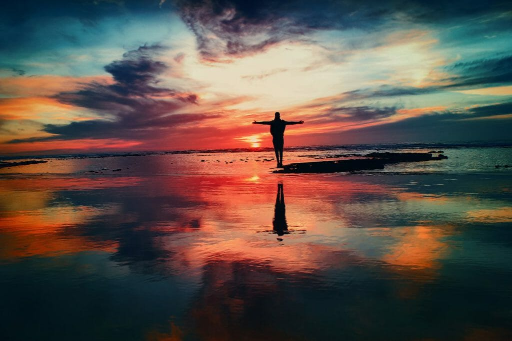 Una foto de la silueta de una persona parada en una playa al atardecer - una gran idea fotográfica