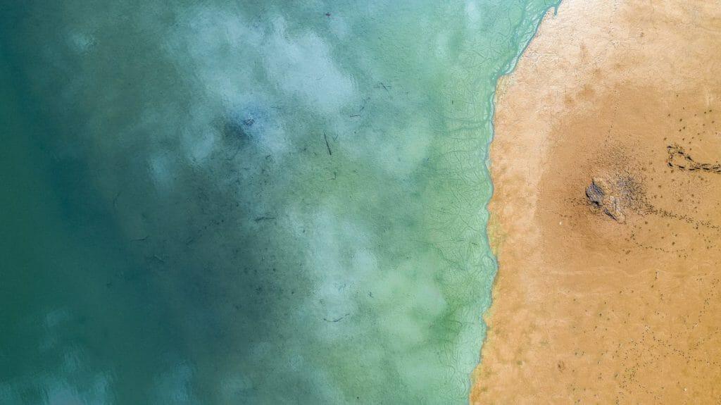 Una foto aérea del mar y la arena uno al lado del otro