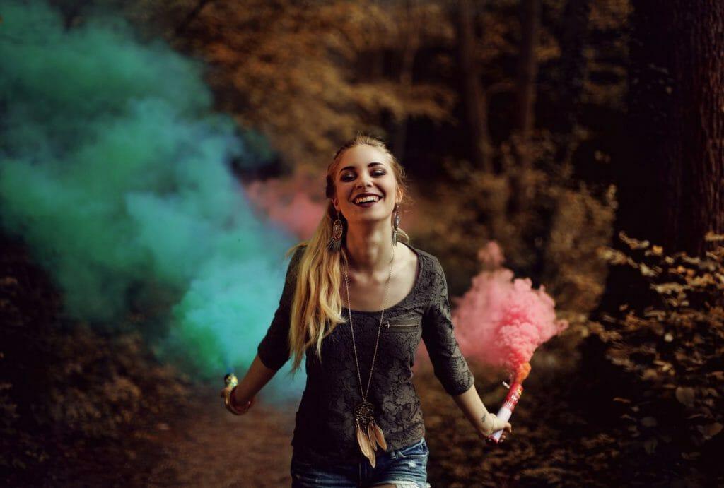 Una mujer sonríe sosteniendo plumas de humo rojo y verde
