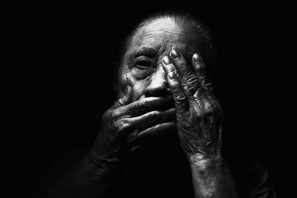 Una fotografía en blanco y negro de una anciana con las manos sobre la cara
