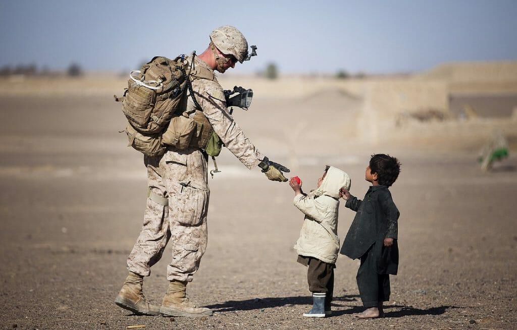 Una foto de un soldado hablando con niños pequeños en una zona de guerra