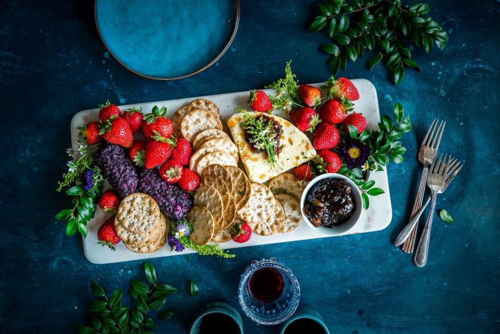 Una foto de comida que muestra un plato de galletas y fruta en una mesa con hierbas y cubiertos