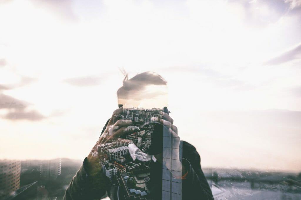 Una foto de doble exposición de la silueta de un hombre con un paisaje urbano dentro de su cabeza