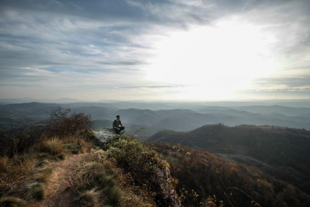 Una foto de un hombre sentado en una colina mirando a una cadena montañosa