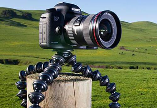 El Gorillapod Focus de Joby con una cámara digital DSLR montada en un poste de la valla en un campo