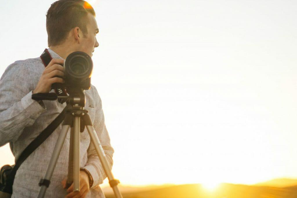 Un hombre coloca una cámara en un trípode para capturar una toma de la puesta de sol