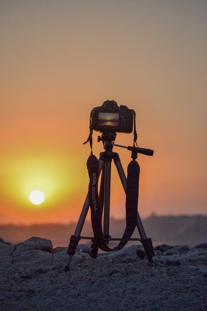 Una cámara digital DSLR montada en un trípode sobre la arena, durante una puesta de sol en la playa