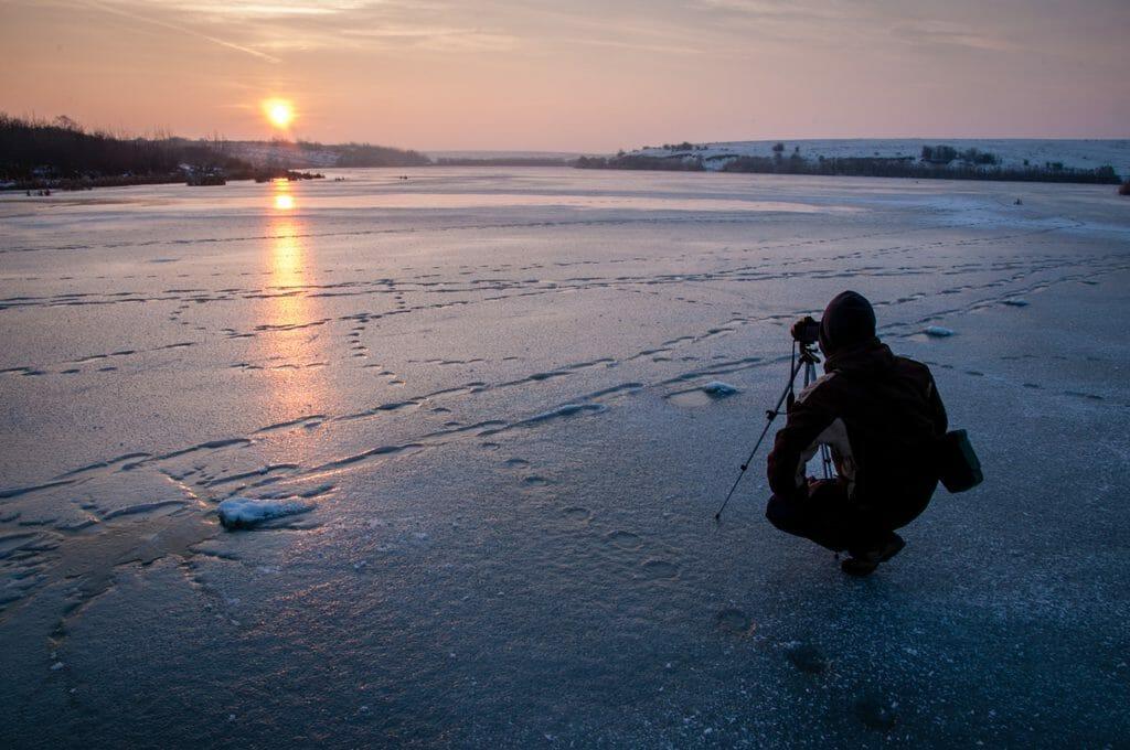 Un hombre se paró en un lago helado con una cámara y un trípode tomando una imagen del amanecer