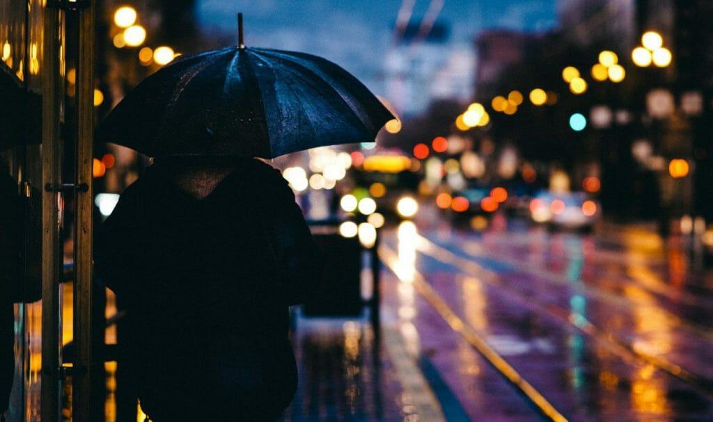 Una foto nocturna de cuadro completo de una persona bajo un paraguas mirando a una calle mojada