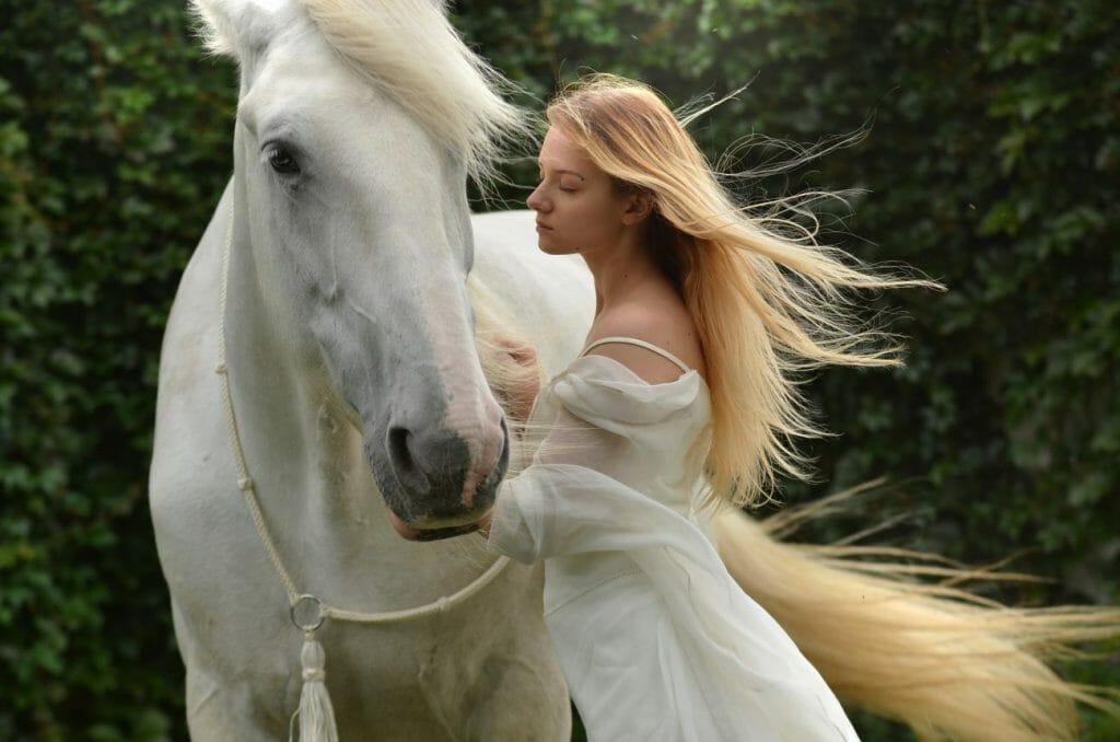 Una foto de una mujer con un vestido blanco junto a un caballo blanco