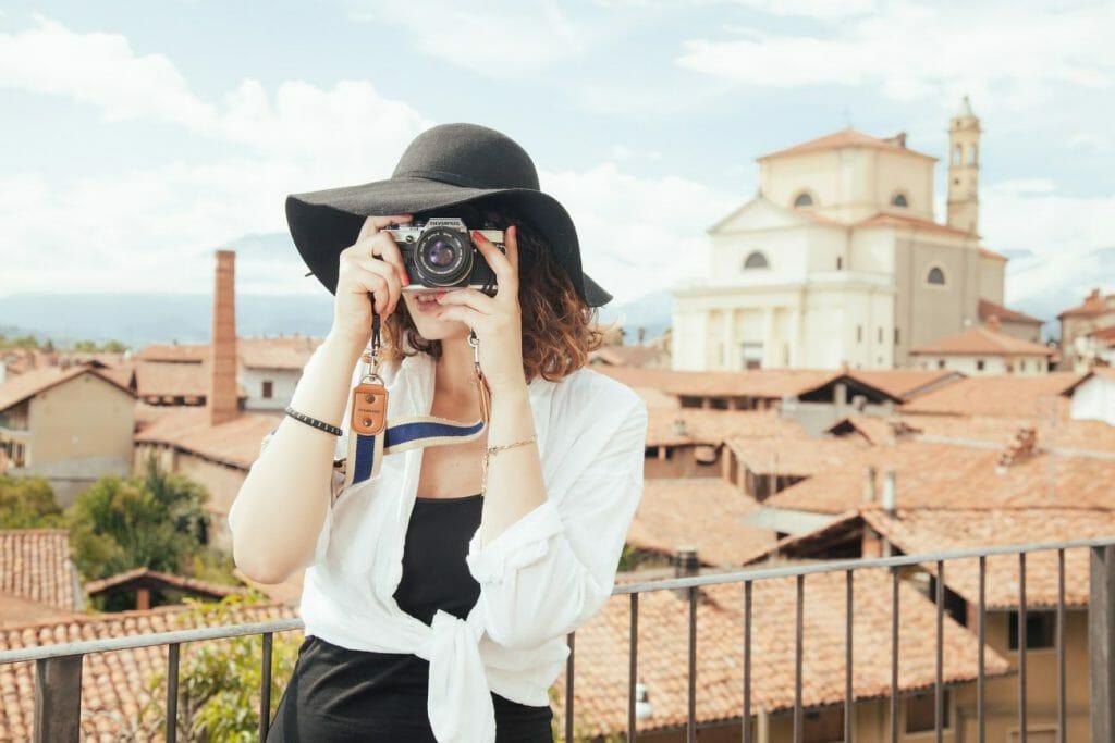 Una foto de una mujer con sombrero tomando una fotografía con una cámara.