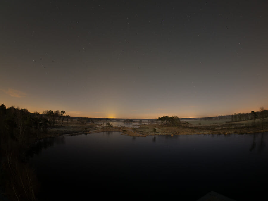 A night shot of a Belgian landscape showing orange light pollution on the skyline